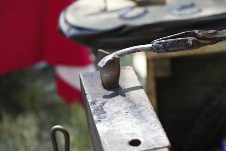 incus: a blacksmith makes a horseshoe with a hot iron close-up