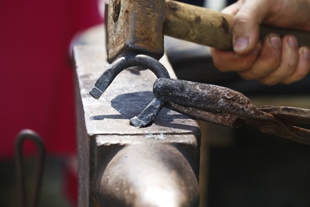 incus: a blacksmith makes a horseshoe with a hot iron close-up