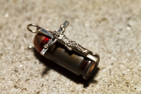 a Bullet and pectoral cross , abstract religion