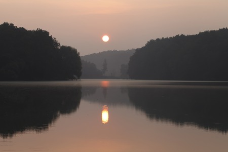 beautiful landscape during sunrise on the lake, the suns reflection in the water and the shade of trees