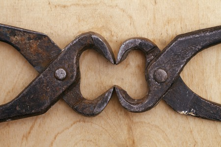 a old vintage tongs tool on a wooden background Stock Photo