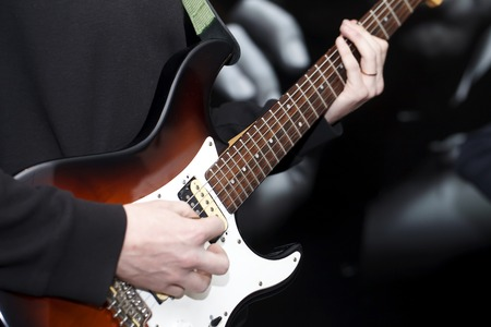 jamming: a young musician playing electric guitar close-up