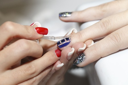 beautiful woman body: manicurist makes the new gel polish manicure, close-up, beauty and body care