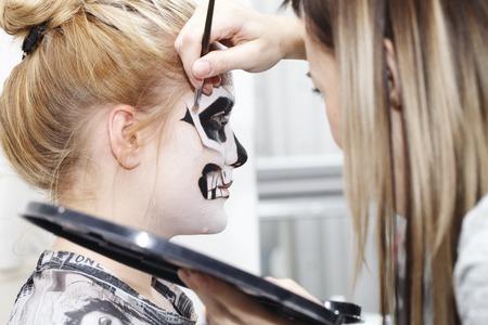 ハロウィーン、黒と白のスカルの顔アートで美しい少女