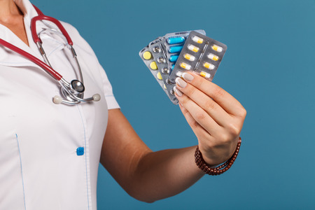 青色の背景にスタジオで手にクローズ アップの丸薬を持つ医師