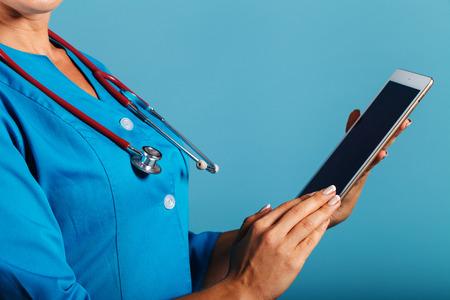 Doctor de la mujer joven con una tablilla en la mano en el estudio, la medicina, la tecnología moderna Foto de archivo