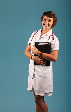 スタジオ内のフォルダーの肖像若い女性医師 写真素材