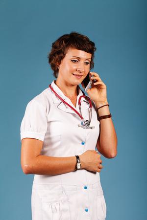 携帯電話で若い美しい医者の肖像画