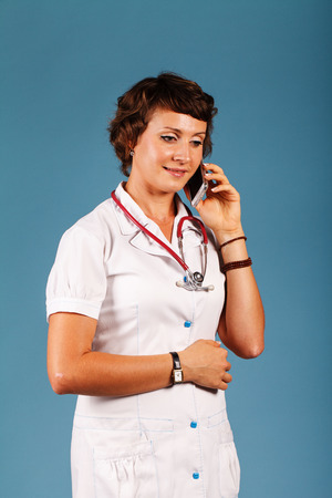 Portrait of a young beautiful doctor with phone Banco de Imagens