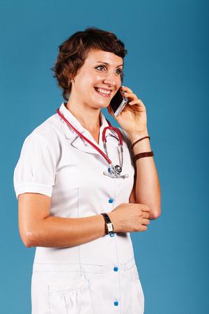 スタジオに電話で若い美しい医者の肖像画 写真素材