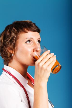 フレッシュ ジュースのグラスを持つ若い女性医師