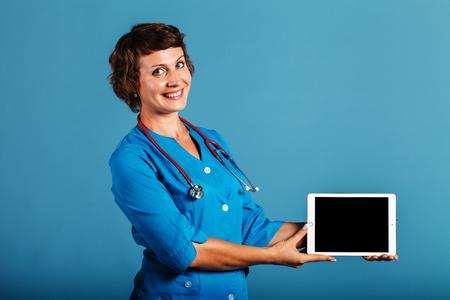 彼の手の空スペースでタブレットを持つ医師