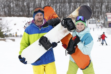young couple snowboarders rejoice and be glad