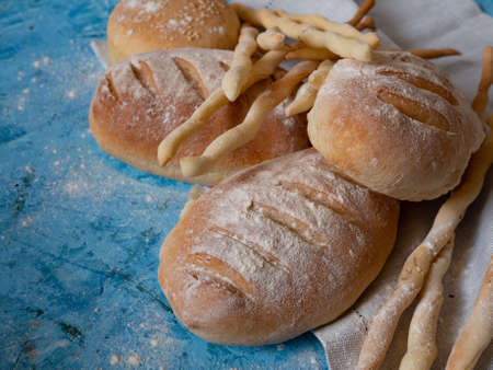 Italian gressini bread sticks and bread. Delicious aromatic pastries on a blue textured background.