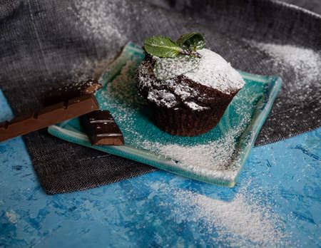 Delicious chocolate muffin with powdered sugar and mint sprig on light blue textured background