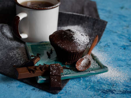 Sweet dessert time. Chocolate delicious muffin with powdered sugar. Mug of black tea and milk chocolate.