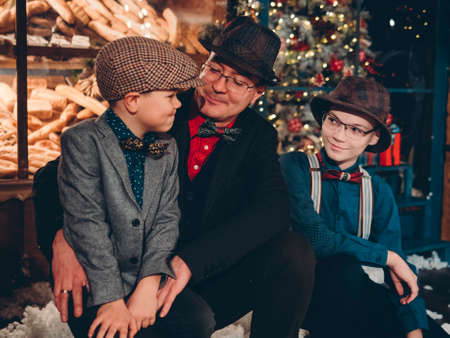Happy father with his sons on New Years Eve in festive New Years decorations. Stylishly dressed family in retro vintage clothing for the new year. Reklamní fotografie