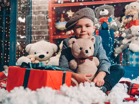 Happy new year and christmas.Cute stylishly dressed boy with a teddy bear and a box with a gift in a beautiful new year decorations with artificial snow and a showcase with many toys.