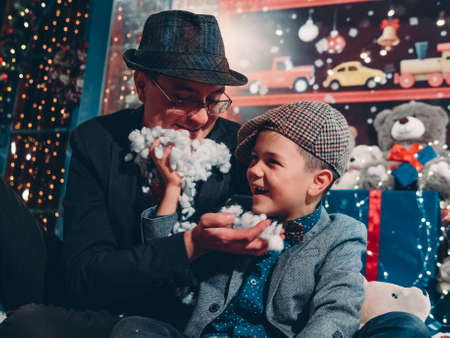 New Years festive mood. A happy father with his son have fun and make an artificial New Years beard.
