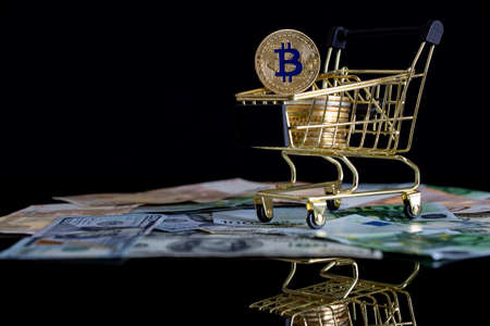 Bitcoins in gold color in a consumers basket on a black background. Cryptocurrency, digital money and electronic payments.