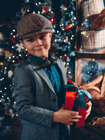 Happy child with a gift in his hands. Stylishly dressed in a retro style boy on the background of a beautiful New Year tree.
