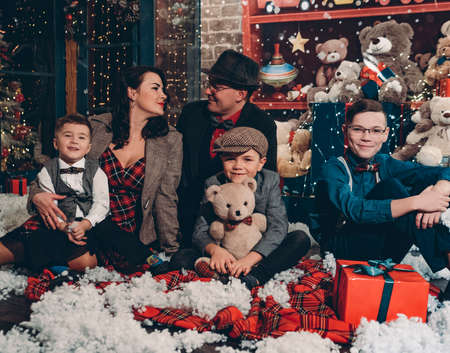 Big happy and beautiful family on New Years Eve or Christmas Eve. Happy parents and their three sons in festive New Year decorations. Christmas family in retro style. Reklamní fotografie