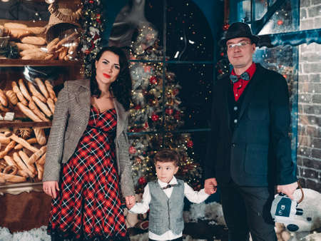 Beautifully dressed in retro style parents with their little son on the eve of New Years holidays. Festive Christmas vintage happy family atmosphere.