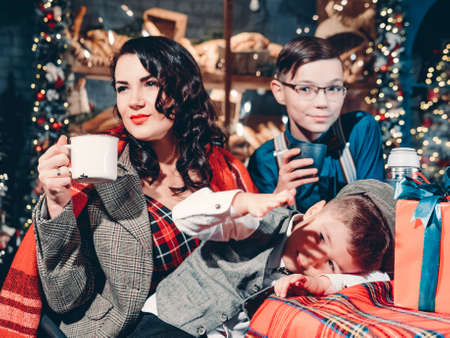 Festive mood of a happy family on the eve of New Years holidays. New Years scene of a happy mom with her sons dressed in a stylish vintage style.