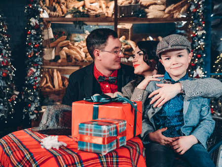 Happy family on the eve of New Years and Christmas. Christmas scene of loving parents and their son dressed in retro style. Reklamní fotografie