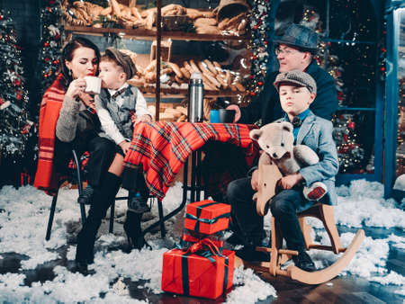 Happy family dressed in retro style in beautiful New Years decorations. Happy New Years and Christmas Eve Family Celebration Concept.