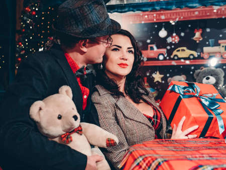 A beautiful couple in love dressed in retro style sits at a table in beautiful New Years decorations.