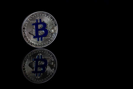 Bitcoin close-up on a black background with a reflective surface.