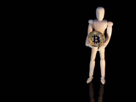 Conceptual photo of cryptocurrency. Small wooden man holding a round bitcoin coin in golden color. The object is shot on a reflective black surface. The photo has a lot of space for design text.