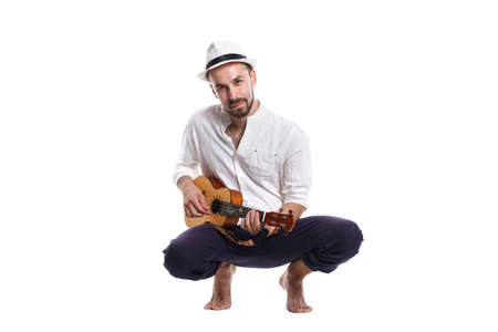 Attractive young Caucasian male with ukulele isolated on white background. Reklamní fotografie