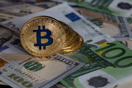 Bitcoins close-up on the background of paper bills of different countries.