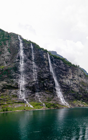 panoramic view to Seven Sisters cascade waterfall and Geirangerfjord in Norway Stok Fotoğraf