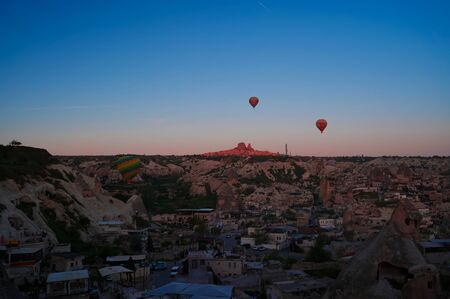 Sunrise panoramic view to Goreme,Uchisar city and flying balloons over pigeon valley Cappadocia, Turkey