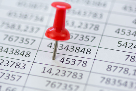 close up image: Close Up image of financial data with a red Pin.