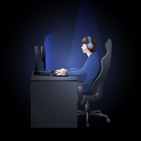 collectible: Young man sitting at the table and playing computer. Side view. Cyber sport concept.
