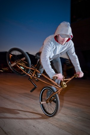 flatland: Bmx flatland training at night in a  city.