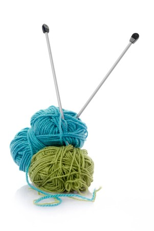 Balls of green and blue  knitting wool or yarn, with silver knitting needles.