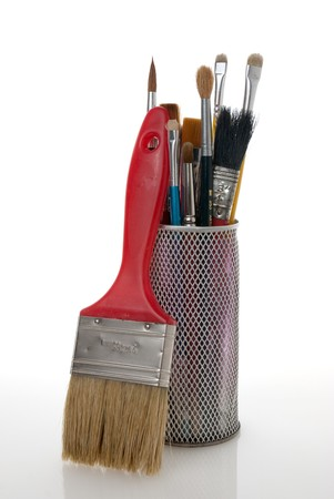 Paintbrushes in a metal mesh holder on white background. photo