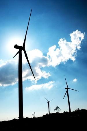 recursos renovables: Turbina de viento en la espalda luz del sol con cielo azul y las nubes.  Foto de archivo