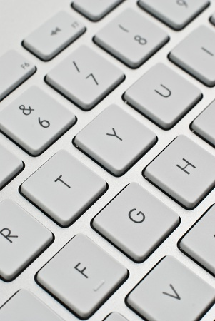 Closeup perspective of a modern aluminum keyboard, focus on center keys. photo