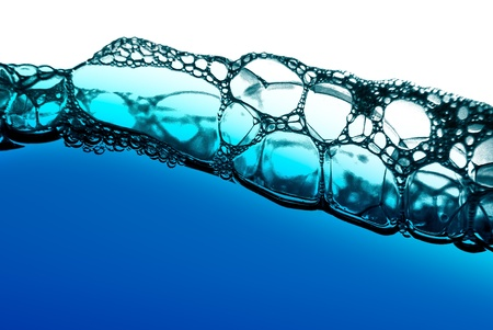 Air bubbles in blue water on white background. photo