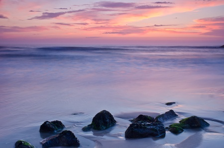 Sunset on a beach, beautiful sky and silky water arround rocks. Stock Photo - 9645109