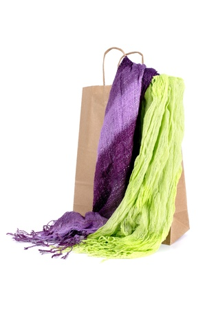 bufandas: Shopping brown craft paper bag with two scarves on white background.