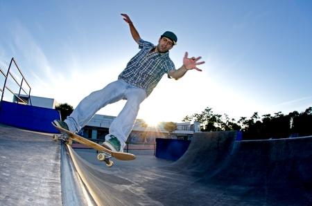 grind: Skater en una rutina al atardecer en el skatepark local. Foto de archivo