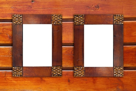 Two blank wooden frames on wooden wall. photo