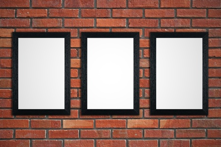 Three black picture frames on red brick wall. photo